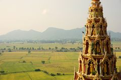 Top of Buddha temple with rice field background Royalty Free Stock Photo