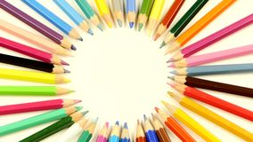 Top of bunch of colored pencils on white, rotation stock footage