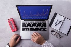 Top of businessman using laptop computer with stock chart market on screen. stock photography
