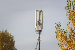 Top of a cellular radio tower, Antenna against the background of the autumn forest and the blue sky with clouds stock photography
