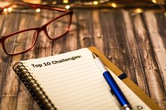Top 10 Challenges on a notebook as motivational business concept. Goals for success on a notebook; motivational concept on dark wood planks for vintage retro royalty free stock photo