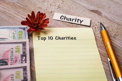 Top 10 Charities concept on notebook and wooden board Royalty Free Stock Images