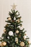 The top of a Christmas artificial tree standing at home. Beige golden shiny star at the top of the tree. Decorating a Christmas