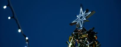 The top of the Christmas tree,against the background of the night sky, festive mood gerland light Holidays New Year royalty free stock photos