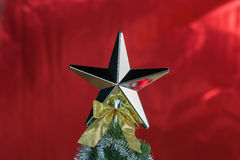 Top of Christmas tree decorated with star in bright red shiny background Royalty Free Stock Photos