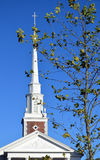 Top of Church with Cross New England foliage. Tree next to church with leave almost gone Royalty Free Stock Photo