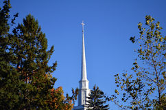 Top of Church with Cross New England foliage. Tree next to church with leave almost gone big pine trees on left Stock Photo