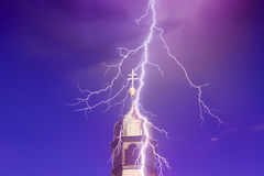 Top of church tower with lightning. And blue and purple sky Royalty Free Stock Photos