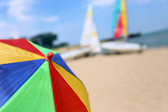 Top of a Colorful Beach Umbrella against the Sky and boat and sea Stock Images