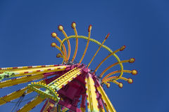 Top of colorful carnival ride. Colorful top of a spinning carnival ride against a bold blue sky stock image