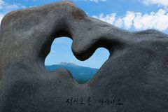 Top crater of hallasan mountain volcano seen through a stone sculpture in a park in Seogwipo, Jeju Island, Korea royalty free stock image