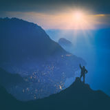On the top of Crimea. Instagram stylisation. Man standing on the top of mountain with raised hand. Sunrise above the Yalta city on a Black sea coast of Crimea Stock Photos