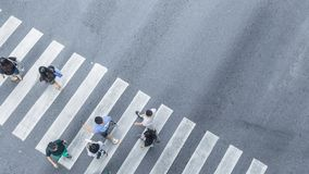 The From the top crosswise view of people walk on street pedestrian crossroad in the city street ,bird eye view. From the top crosswise view of people walk on stock images