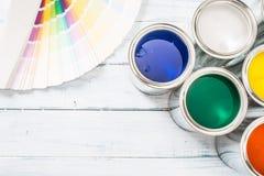 Top de cepillos de las latas de la pintura de la visión y paleta de colores en la tabla fotografía de archivo libre de regalías