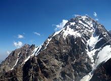 Top de la montaña nevosa de la roca en fondo nublado Foto de archivo