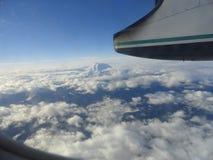 Top de la montaña sobre las nubes mientras que vuela Fotos de archivo libres de regalías