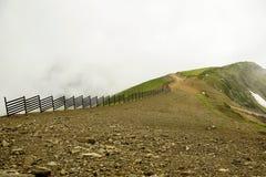 Top de la montaña y del camino en montañas con una cerca está nublado también se empañan Fotografía de archivo libre de regalías