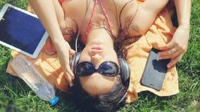 Top de la opinión la mujer joven hermosa en las gafas de sol que mienten en la hierba, escuchando la música Fotos de archivo libres de regalías