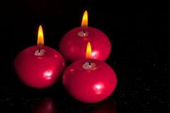 Top de la vista de las velas rojas de la Navidad en el fondo de madera de la tabla Fotos de archivo libres de regalías
