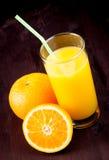 Top de la vista del vidrio lleno de zumo de naranja con la paja cerca de la naranja de la fruta Imagen de archivo libre de regalías