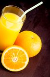 Top de la vista del vidrio lleno de zumo de naranja con la paja cerca de la naranja de la fruta Imágenes de archivo libres de regalías