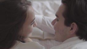 Top de pares jovenes felices que mienten en la cama que lee el primer del libro Hombre hermoso que toca la cara de la mujer ofert metrajes