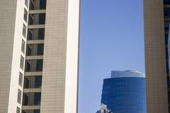 Top de un edificio alto corporativo moderno azul con un diseño rayado que se coloca en el fondo entre un par de yellowis gemelos foto de archivo libre de regalías