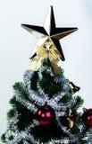 Top del árbol de navidad adornado con la estrella en fondo blanco brillante Foto de archivo