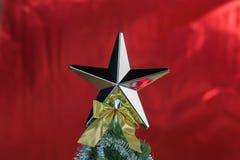Top del árbol de navidad adornado con la estrella en fondo brillante rojo brillante Fotos de archivo libres de regalías