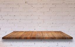 Top del estante de madera con la pared de ladrillo blanca fotografía de archivo