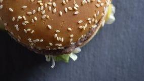 Top del primer abajo de la vista del cheeseburger doble con sésamo en los bollos que giran en el movimiento metrajes