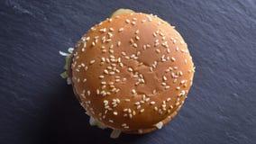 Top del primer abajo del lanzamiento estático del cheeseburger doble con sésamo en los bollos con el fondo aislado metrajes
