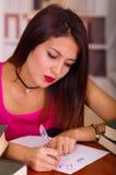 Top del rosa de la mujer que lleva morena joven que se sienta por el escritorio que parece cansado, escribiendo en el papel duran Foto de archivo