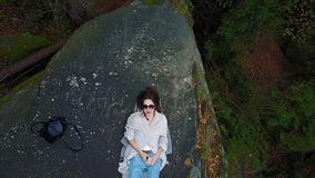 Top down aerial drone image of a forest. Top down aerial drone image of a forest, woman lies on a rock stock video footage