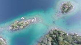 Top down aerial 4k video of topical island with jetty and small cabin surrounded by trees in lake Eibsee, Germany. Top down aerial 4k video sliding forward to stock footage