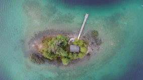 Top down aerial 4k video of topical island with jetty and small cabin surrounded by trees in lake Eibsee, Germany. Top down aerial 4k video ascending upwards to stock footage