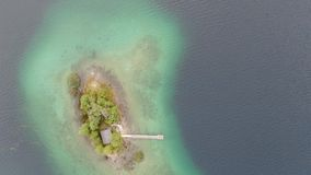 Top down aerial 4k video of topical islands with jetty and small cabin surrounded by trees in lake Eibsee, Germany. Top down aerial 4k video sliding forward to stock video
