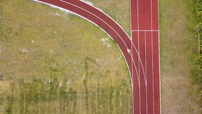 Top down aerial view of a jogger running on red football field tracks.