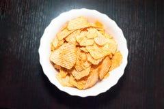 Top-down Ansicht einer weißen Schüssel zerfurchter Kartoffelchips auf dunklem hölzernem Hintergrund stockbild