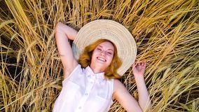 Top down camera spin over woman lying on wheat field and laughing at camera. Top down camera spin over young woman in white cotton dress and big hat lying on stock footage