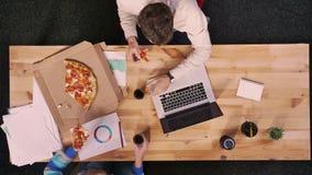 Top down, de zitting van de tijdtijdspanne op het werk twee wordt geschoten collega's eet smakelijke pizza en werkt, houten die c stock videobeelden
