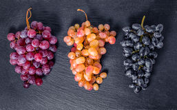 top down of different branches grapes on black slate stone background with empty copy space, close up royalty free stock image