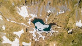 Top and down drone aerial view of an Alpine natural lake during spring season. Snow melting. Italian Alps. Italy royalty free stock photos