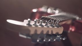 Top down focus shift on electric guitar on a stand, cinematic bokeh.  stock video footage