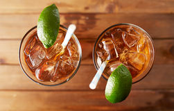 Top down photo of two glasses of iced tea. Two glasses of iced sweet tea with lime and retro paper straws shot overhead on wooden table stock image