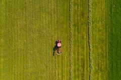 Top down satellietbeeld van een rode tractor die landbouwgrond met een spinnend rek cultiveren stock fotografie