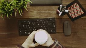 Top down shot of man with cup of coffee typing on keyboard. Top down view of man with cup of coffee typing on keyboard while sitting by wooden table stock video