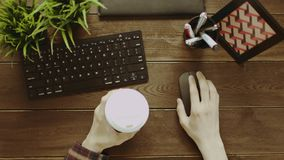 Top down shot of man using computer mouse with cup of coffee in other hand. Top down view of man using computer mouse with cup of coffee in other hand while stock video