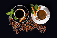 Top down tea and coffee with seasonings. Top down view of tea and coffee surrounded by beans with seasonings on saucers over black background Stock Images