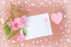 Top down Valentine card of pink heart shaped candle and bouquet Stock Photo